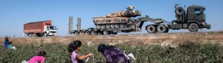 AKCAKALE, TURKEY - OCTOBER 12: Turkish military vehicles carrying tanks head to the Syrian border as farmers work in a cotton field on October 12, 2019 in Akcakale, Turkey. The military action is part of a campaign to extend Turkish control of more of northern Syria, a large swath of which is currently held by Syrian Kurds, whom Turkey regards as a threat. U.S. President Donald Trump granted tacit American approval to this campaign, withdrawing his country's troops from several Syrian outposts near the Turkish border. (Photo by Burak Kara/Getty Images)