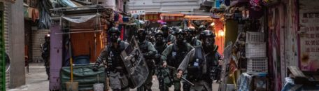 Riot police run through a market during a protest in the Wan Chai district of Hong Kong, China, on Saturday, Nov. 2, 2019. Hong Kong police fired multiple rounds of tear gas at protesters who rallied for a 22nd consecutive weekend despite authorities denying them a permit to gather. Photographer: Laurel Chor/Bloomberg via Getty Images